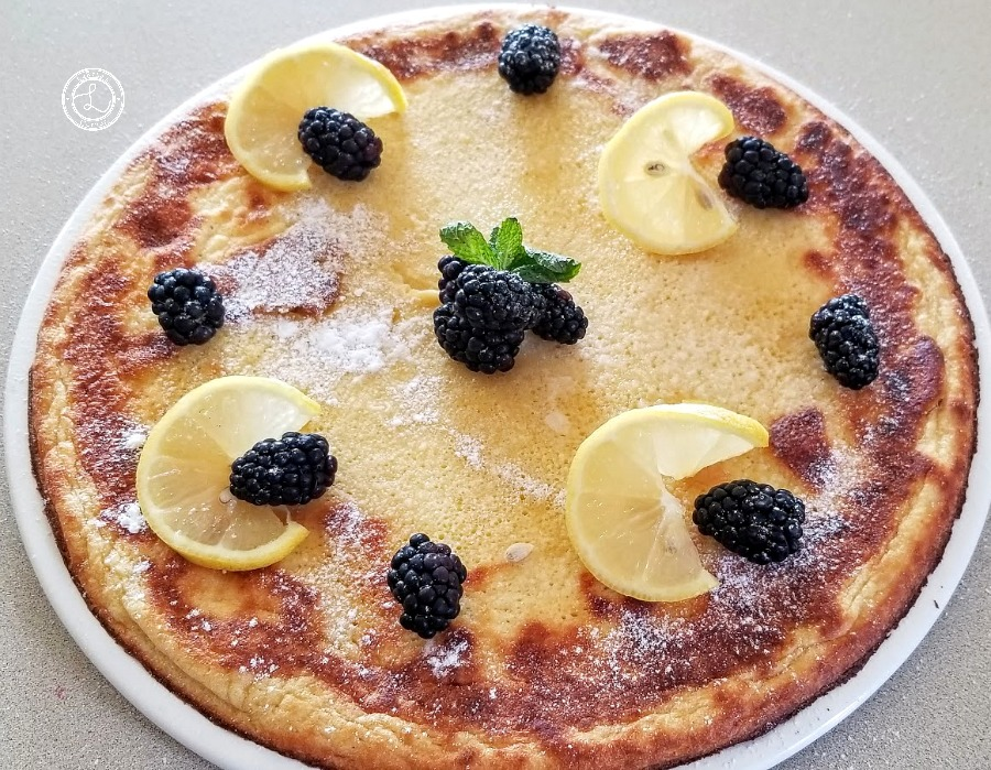 Dutch Pancake on a large plate with lemon slices, blackberries, and mint