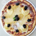 Dutch Pancake on a large plate, with lemon slices, blackberries, and mint