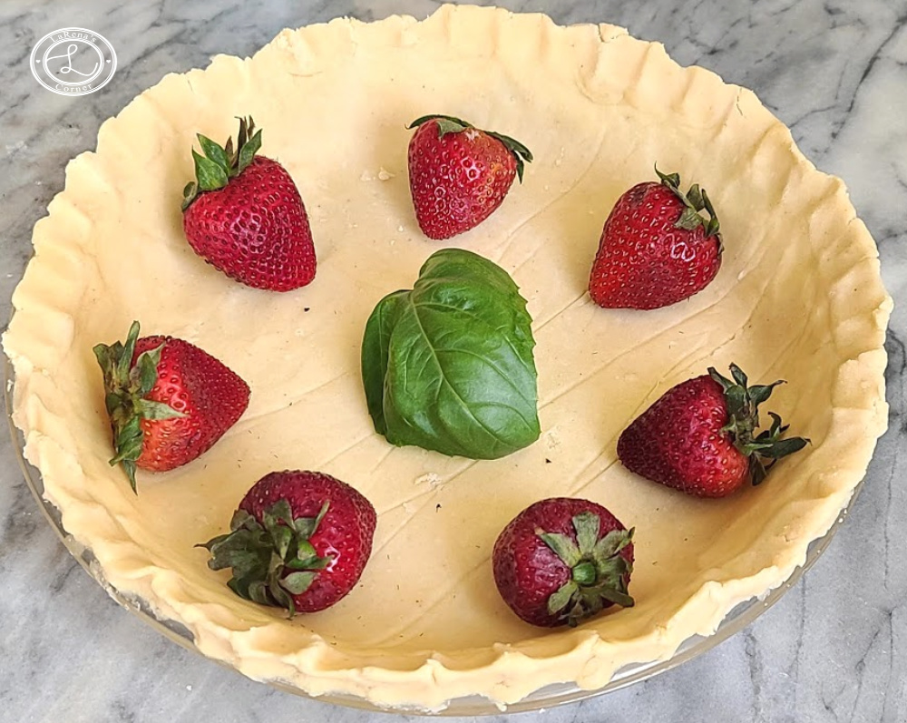 Uncooked Pie Crust with Fresh Strawberries and a basil leaf to decorate the inside.