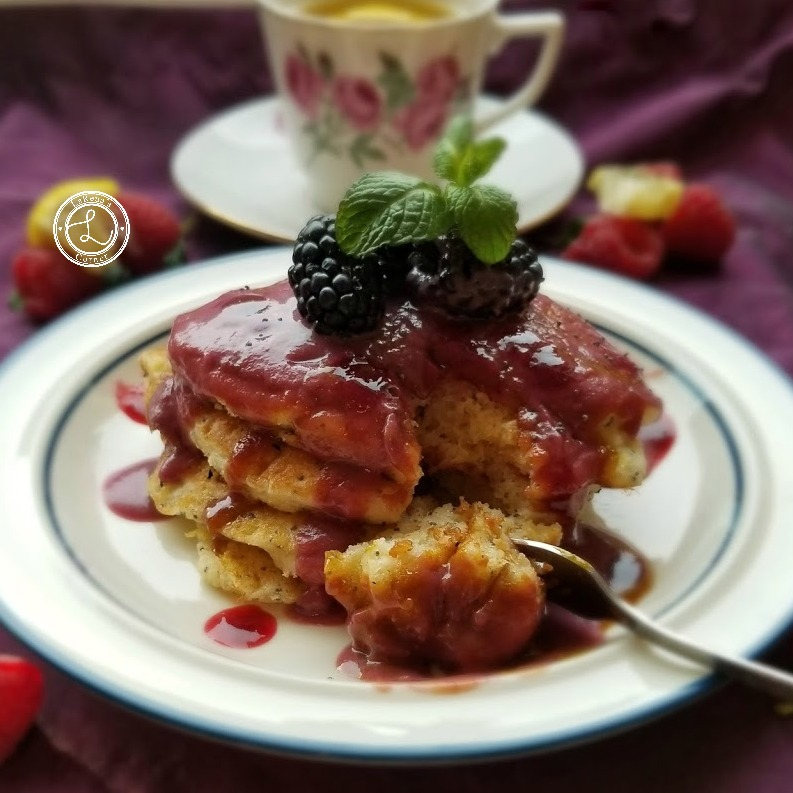 Lemon Poppyseed Pancakes with blackberry coulis syrup and a coffee cup and saucer.