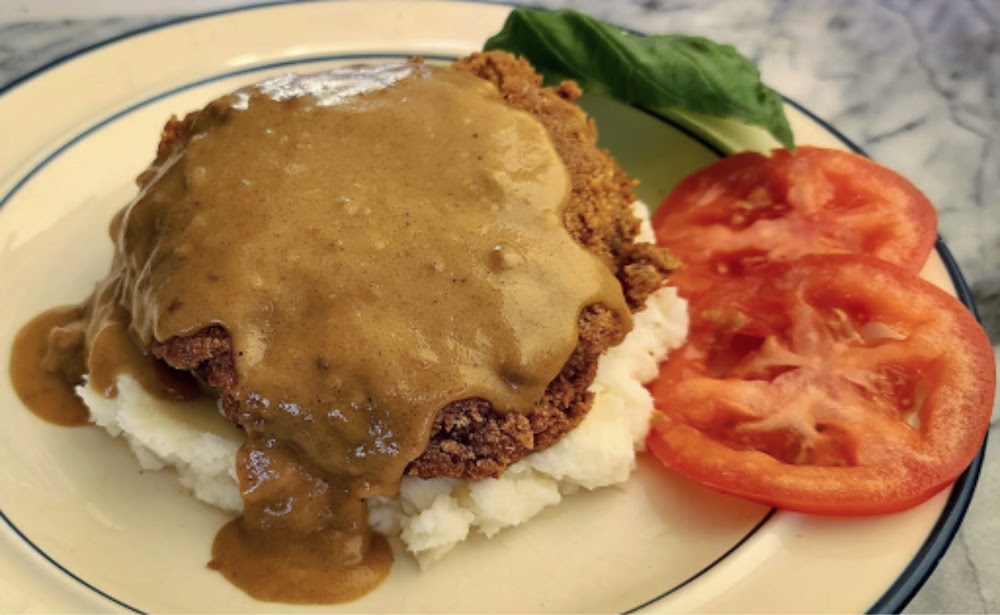 Chicken Fried Steak on top of Cauliflower mash with gravy, tomato slices, and basil leaf.