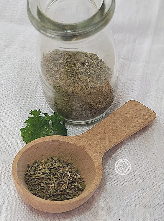 Homemade Italian Seasonings in a bottle and on a wooden spoon