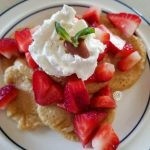Swedish Pancakes on a plate with cut up strawberries, whipped cream and a sprig of mint.