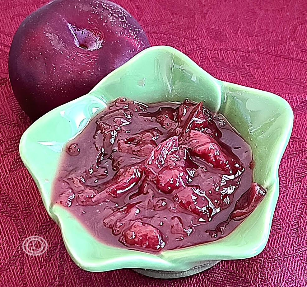 A plum and a bowl of preserves