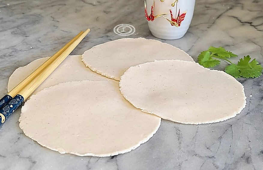 Gluten-Free Potsticker Dough 4 wrappers in a circular pattern with chop sticks, cilantro, and a saki cup with two origami cranes
