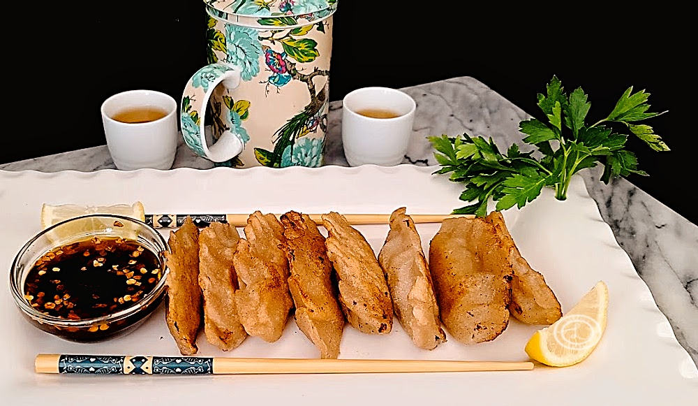 A rectangle platter of gluten-free ground-turkey potstickers with dipping sauce, tea cups, teapot, and chopsticks