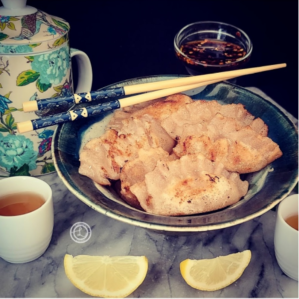 A bowl of gluten-free ground-turkey potstickers, with lemon wedges, tea cups, teapot and chopsticks.