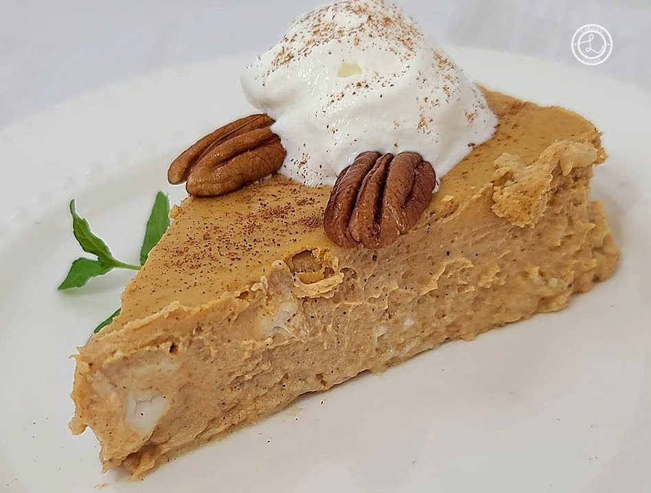 A piece of Crustless Pumpkin Cheesecake on a plate with whipped cream and toasted pecans