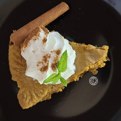 Piece of pie with whipped cream, cinnamon, mint, and cinnamon stick