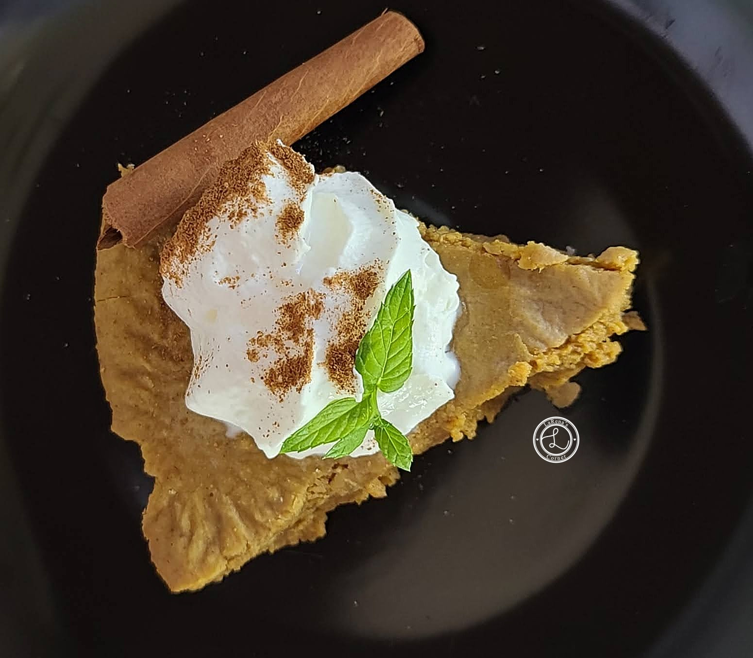 Piece of Gluten-Free Crustless Pumpkin Pie with whipped cream, cinnamon, mint, and cinnamon stick
