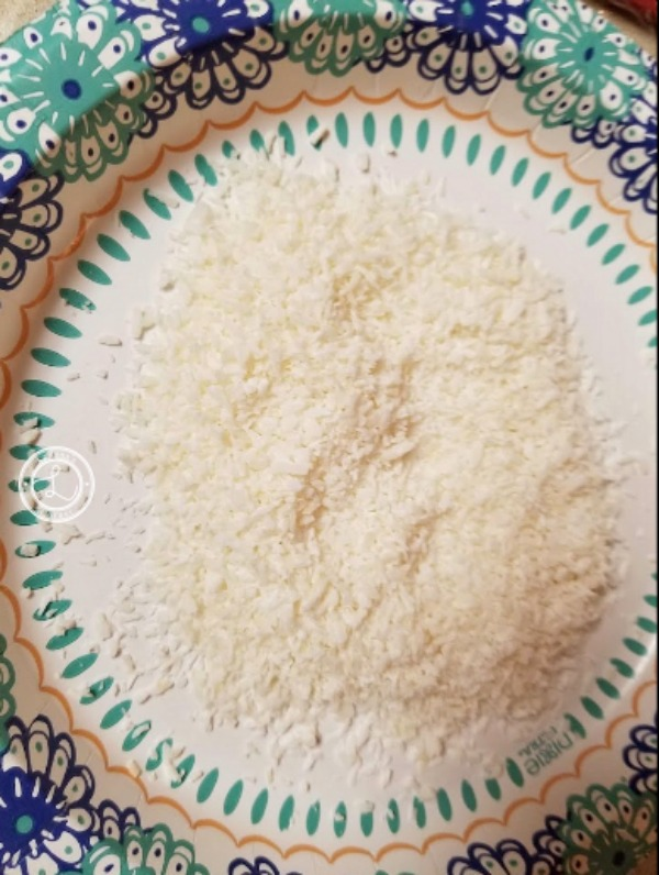 Desiccated coconut and monk fruit sweetener on a plate.
