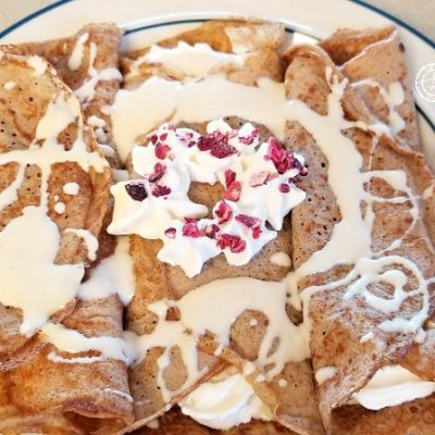 Gluten-Free Pepperkaka Crepes decorated with whipped cream candied cranberries and vanilla sauce