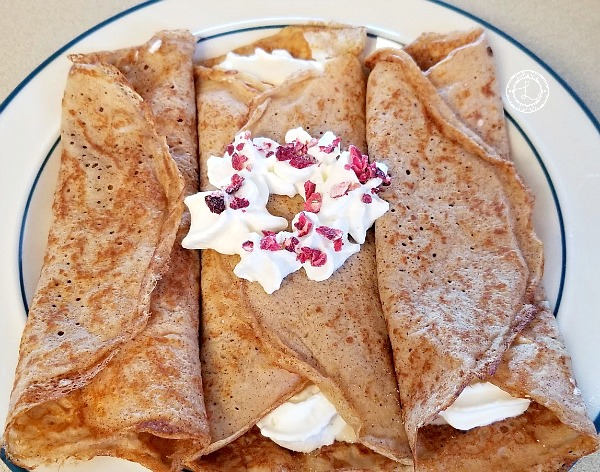Crepes with whipped cream and candied cranberries on top