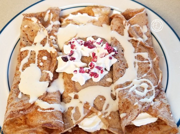 Gluten-Free Gingersnap Crepes decorated with whipped cream candied cranberries and vanilla sauce