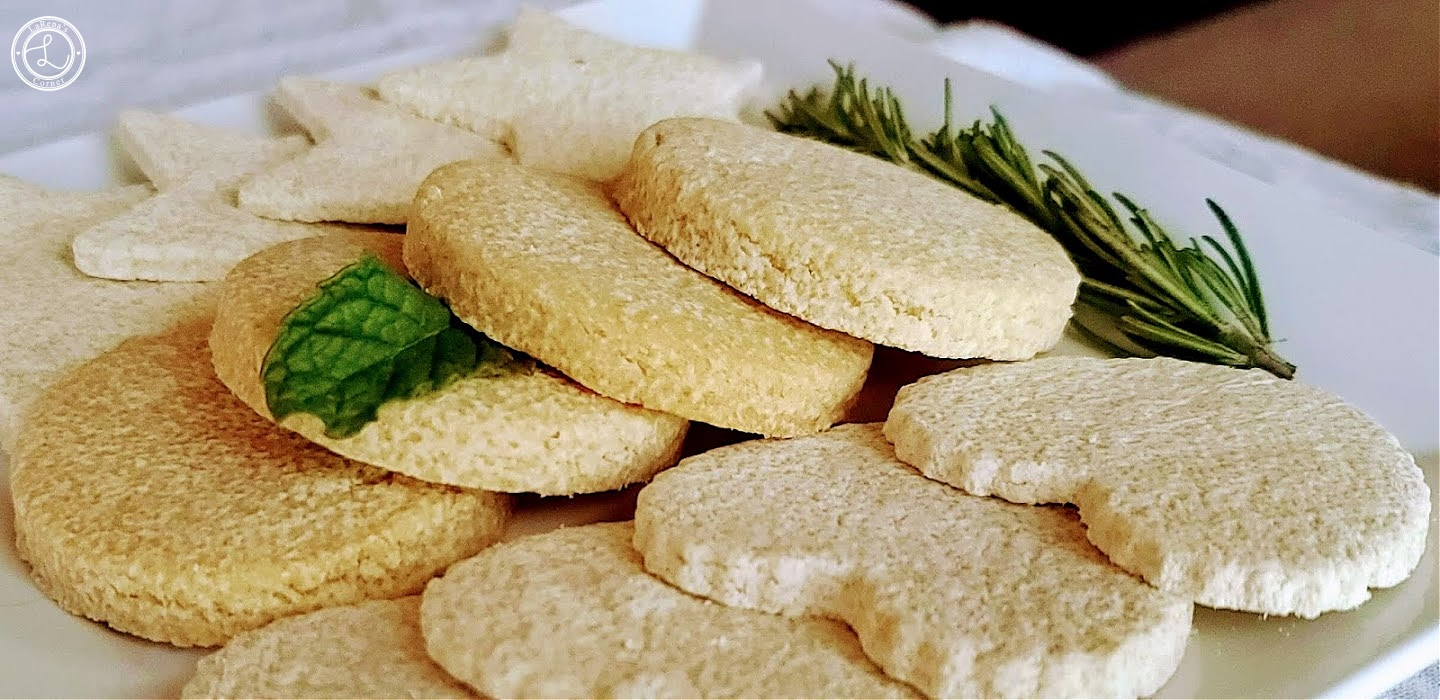 Sugar Cookies on a white plate with rosemary and a sprig of mint