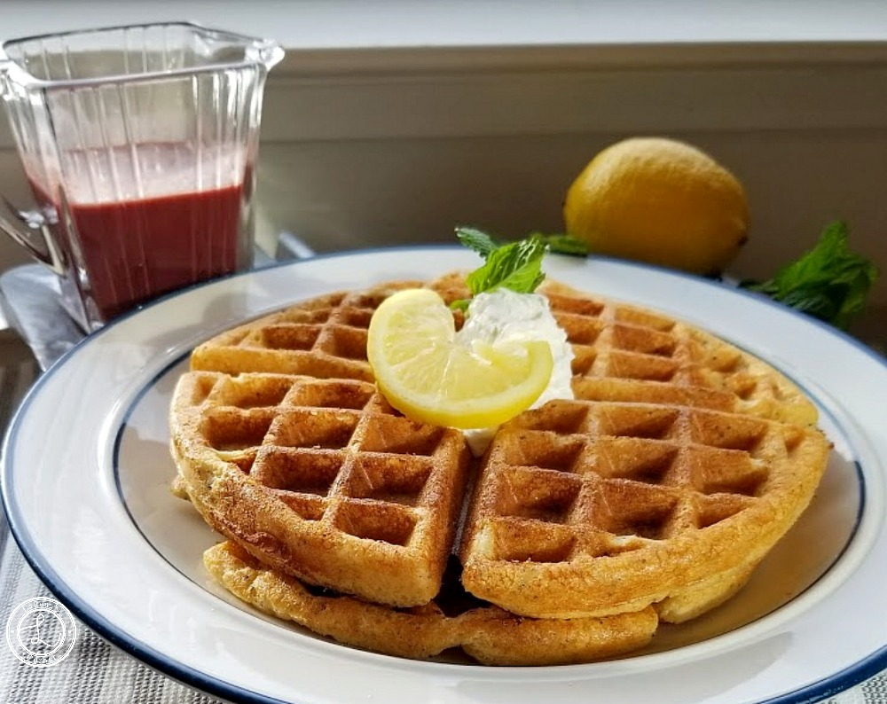 Two thick Sweet-n-Tart Lemon Waffles on a plate with Blackberry Syrup and a lemon in the background