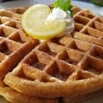 Two Thick Lemon Waffles on top of a white plate with lemon slice, whipped cream, and sprig of mint