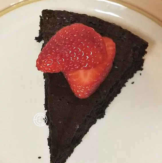 Flourless Chocolate Cake slice on a plate with fresh sliced strawberries