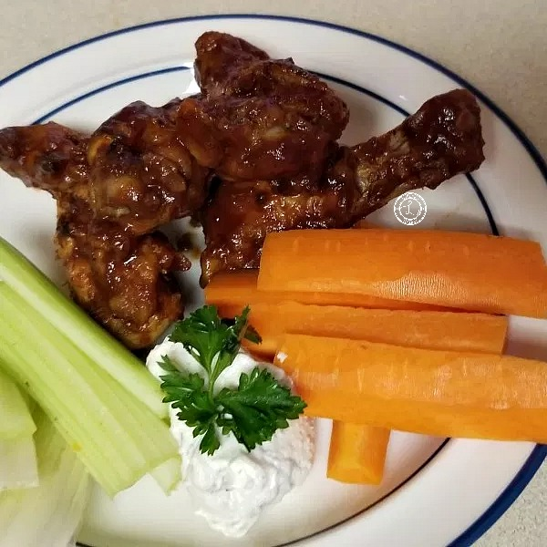 Wings on a plate with carrots, celery, and ranch.