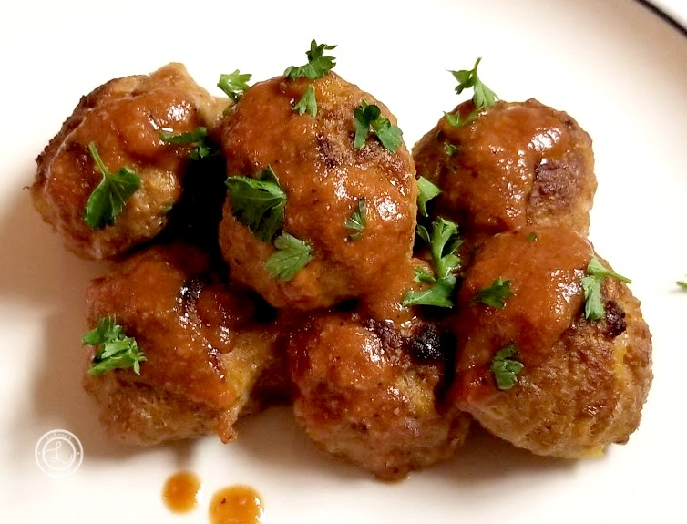 Cooked meatballs with some sauce and ripped parsley