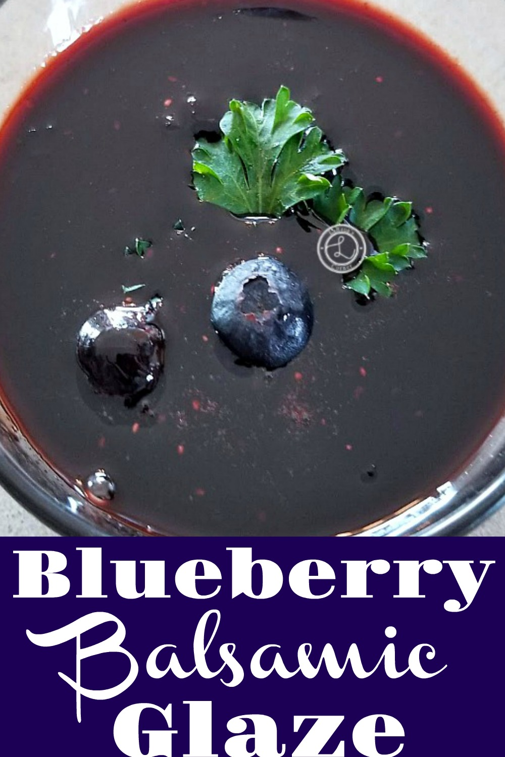 A bowl of Balsamic Blueberry Glaze with a small piece of parsle and two blueberries.