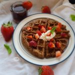 A Strawberry Waffle on a plate with strawberries, mink, and syrup in the background.