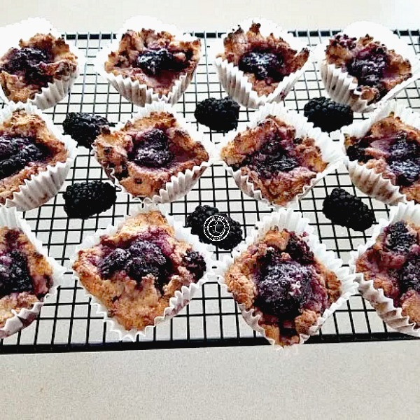 Muffins and blackberries on cooking rack