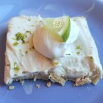 Slice of Key Lime Cheesecake with Coconut Lime Cream and Lime slice