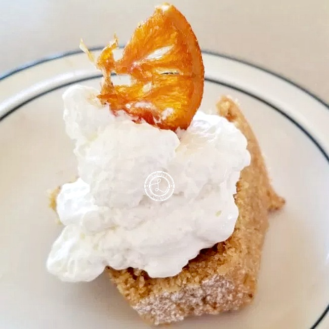A slice of cake with whipped coconut cream and a candied orange slice