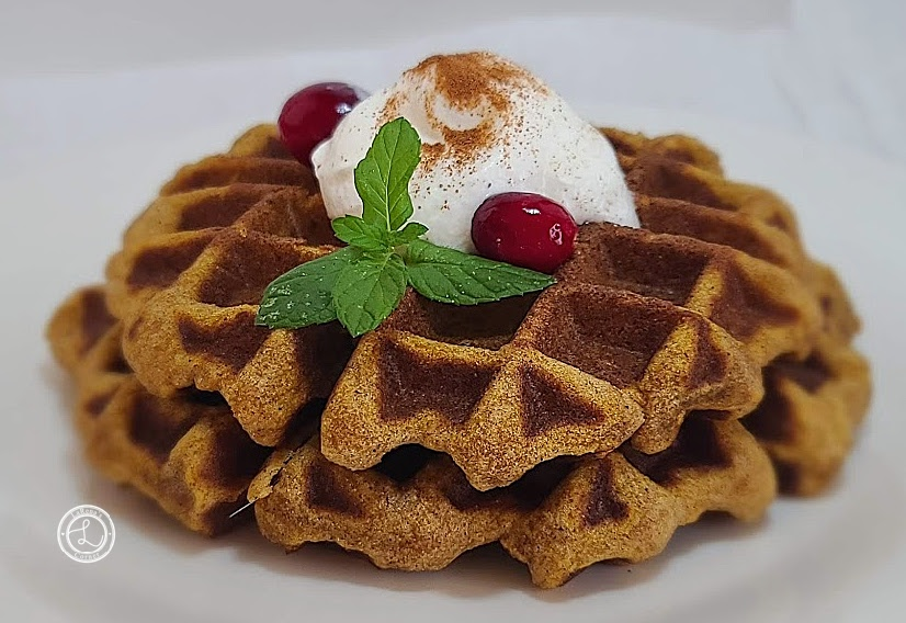 Two waffles with cranberries, whipped cream, cinnamon, and a sprig of mint.
