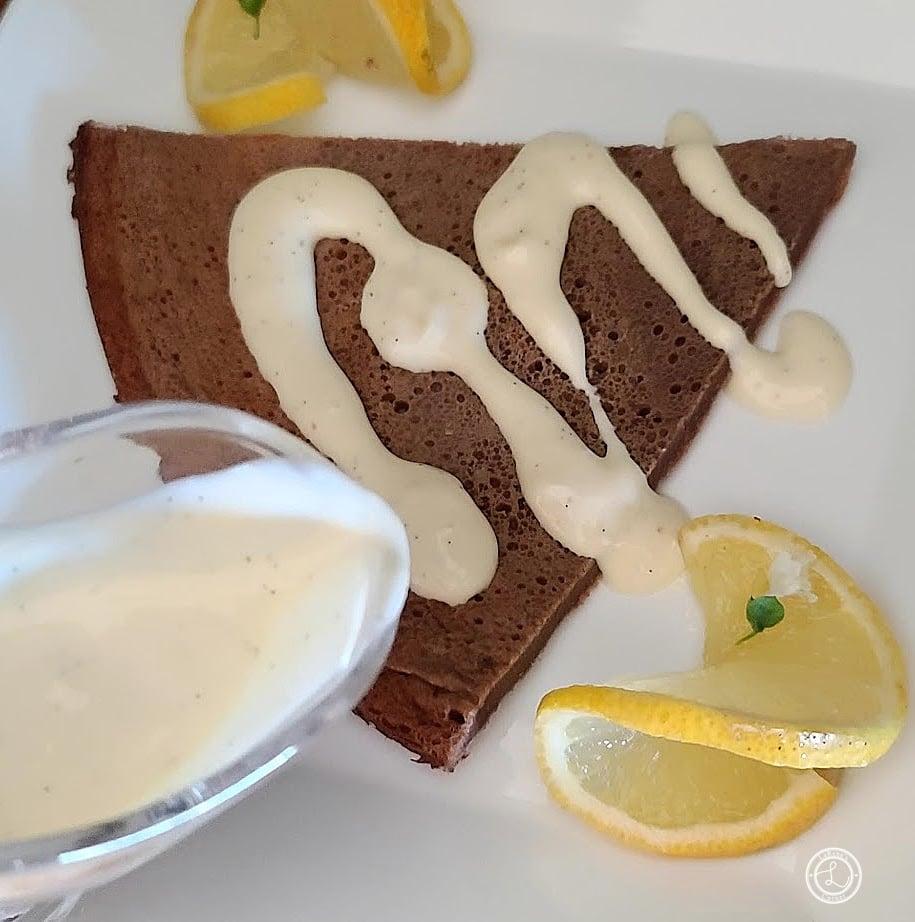 Gluten-Free Vanilla Sauce being drizzled over a Dutch Pancake