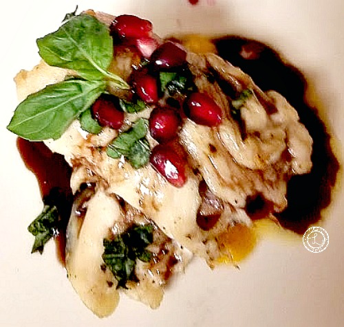 A picture of a decorated Chicken Roulade with pomegranates and basil leaves