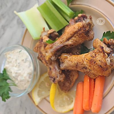 3 chicken wings on a plate with carrots, celery, and homemade dairy-free ranch dip