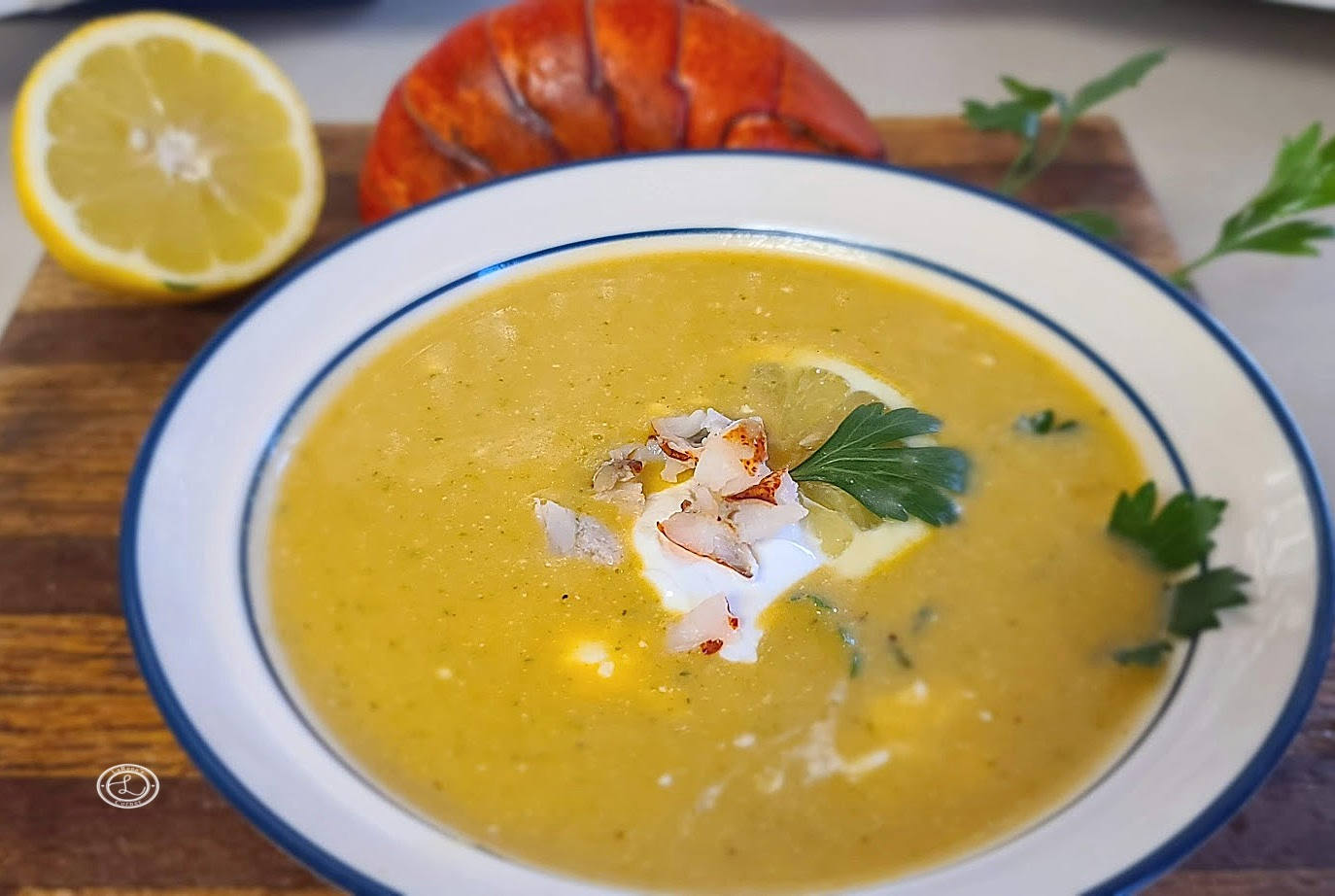 A bowl of soup with a half a lemon and lobster shell in the background.
