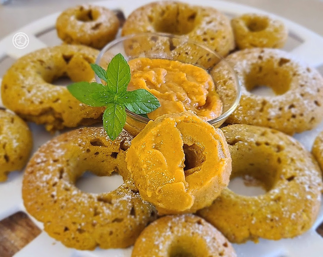 Pumpkin Donuts with a small bowl of glaze and a small donut with glaze on it