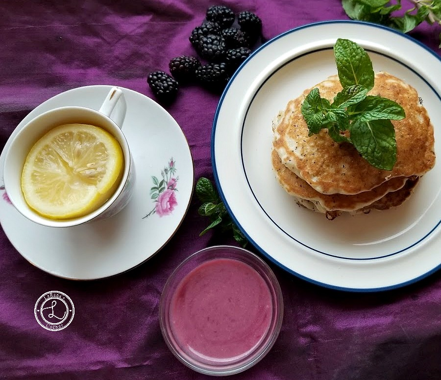 Pictured lemon tea in cup and saucer, with a plate of Gluten-Free Lemon Poppyseed Pancakes and Refined Sugar-Free Blackberry Syrup