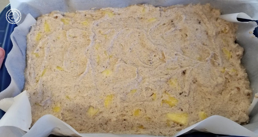 Spreading the pineapple pancake batter in casserole dish