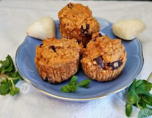 3 muffins on a blue plate with 2 white chocolate hears and sprigs of mint