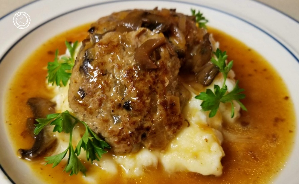 Salisbury Steak, Mashed Potatoes, and gravy with spigs of parsley