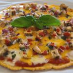 Cooked pizza with a sprig of basil to decorate