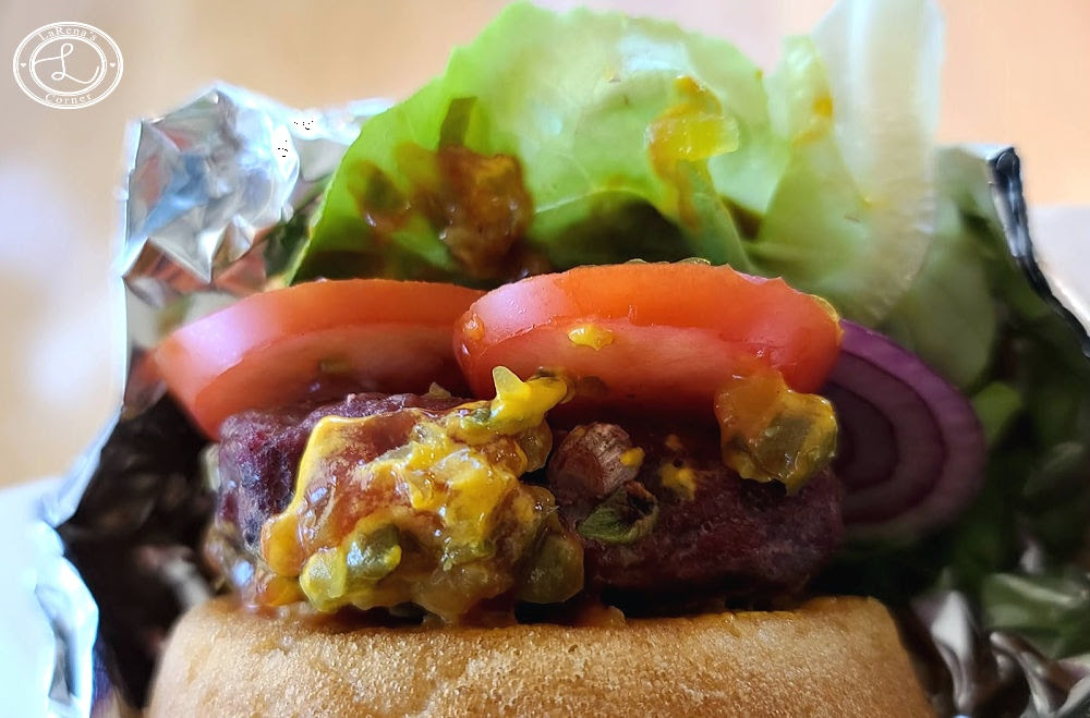 BBQ-Spiced Grilled Buffalo Burger wrapped in parchment and tinfoil to keep clothes keep.