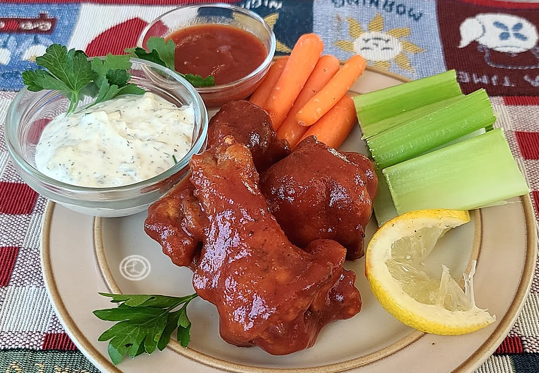 BBQ Chicken Wing Sauce on chicken wings with celery, carrots, ranch, and BBQ sauce.