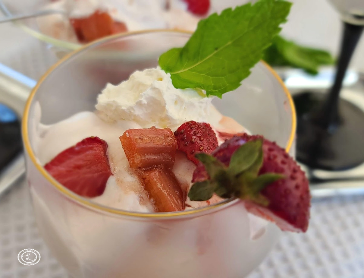 Ice Cream in a cup with strawberry rhubarb compote, whipped cream and a sprig of mint.