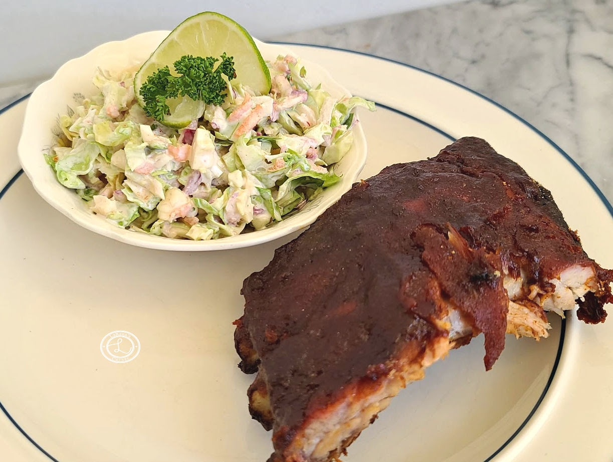 A small Bowl of coleslaw and ribs on a plate.