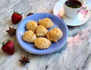 Coconut Macaroons on a plate with a cup of coffee.