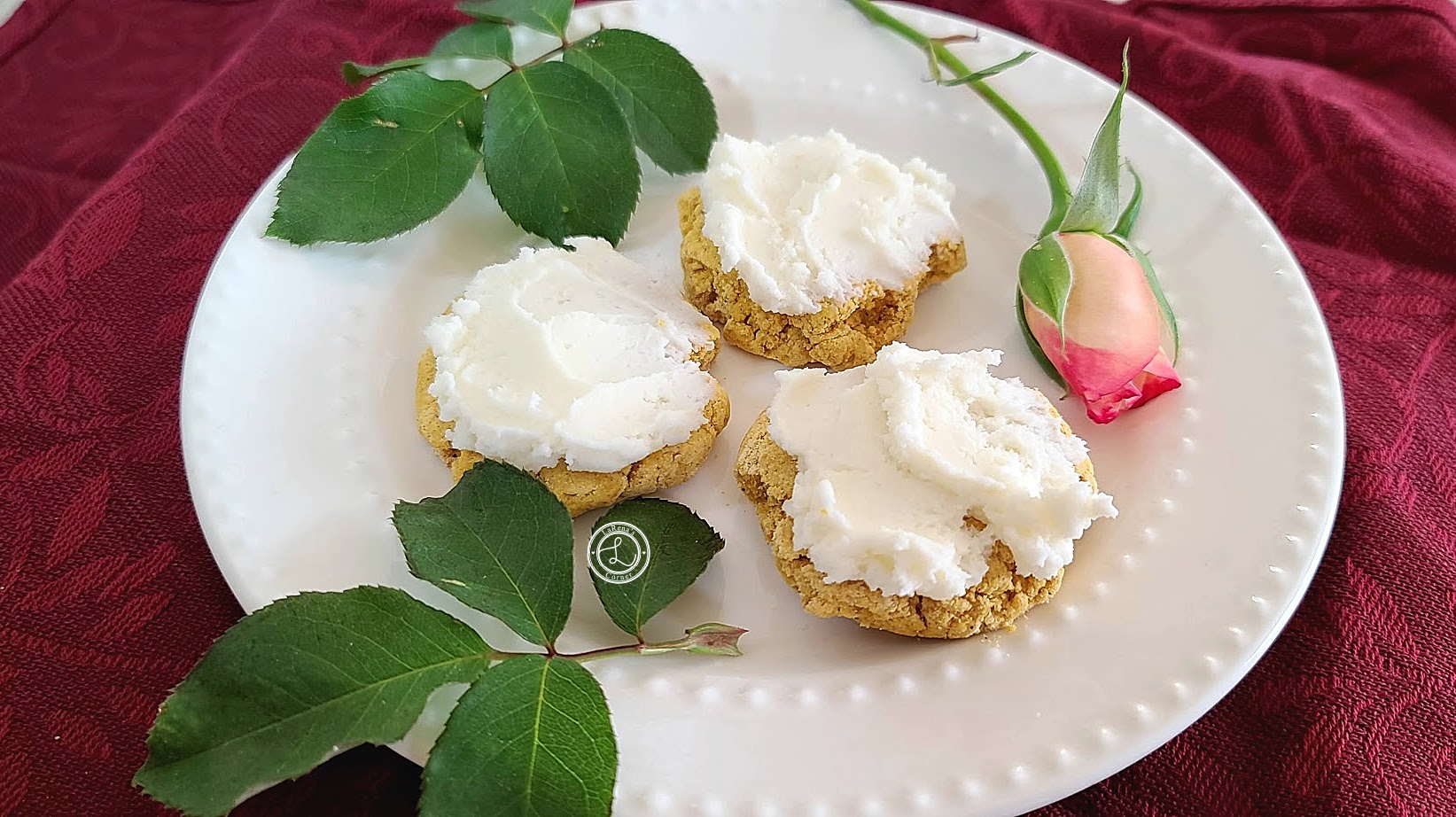 A far away picture of Cream Cheese Cinnamon Frosting on Pumpkin cookies on a plate with leaves and a rose bud.