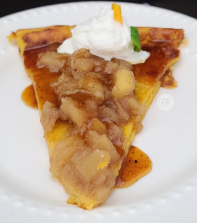 A slice of gluten-free pumpkin Dutch pancake on a plate with cinnamon apples on top