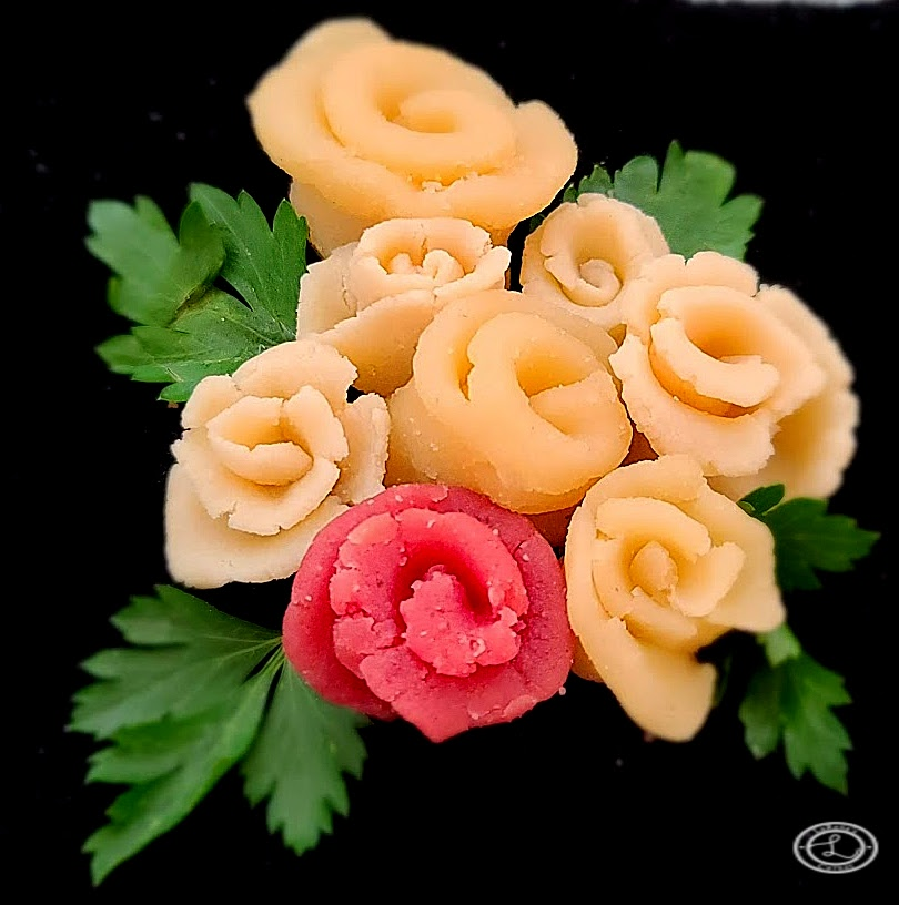A Bouquet of Homemade From Scratch Marzipan Roses one is pinkish red with parsley leaves.